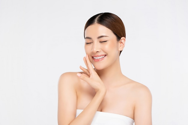 Jeugdige heldere huid vrij aziatische vrouw met hand wat betreft gezicht en ogen het sluiten