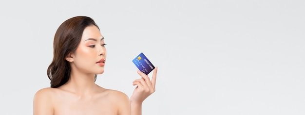 Jeugdige mooie aziatische vrouw die creditcard toont