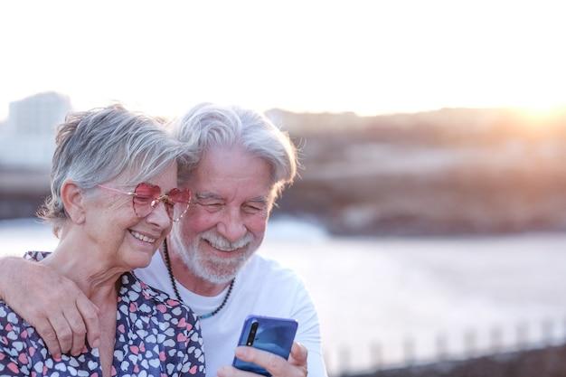 Jeugdige senior paar omarmen in buiten op zee bij zonsondergang met behulp van mobiele telefoon. kaukasisch gepensioneerd genietend van een ontspannen en gelukkige levensstijl