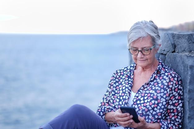 Jeugdige senior vrouw ontspannen in de buitenlucht op zee bij zonsondergang met behulp van mobiele telefoon. kaukasisch gepensioneerd genietend van vrijheid en vakantie Premium Foto