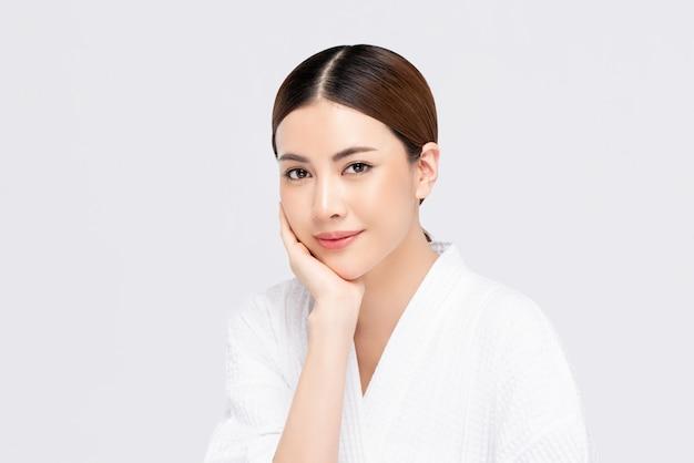 Jeugdige stralende vrij aziatische vrouw met hand wat betreft gezicht