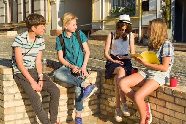 Jeugdvrienden of middelbare scholieren hebben plezier, praten, lezen telefoon