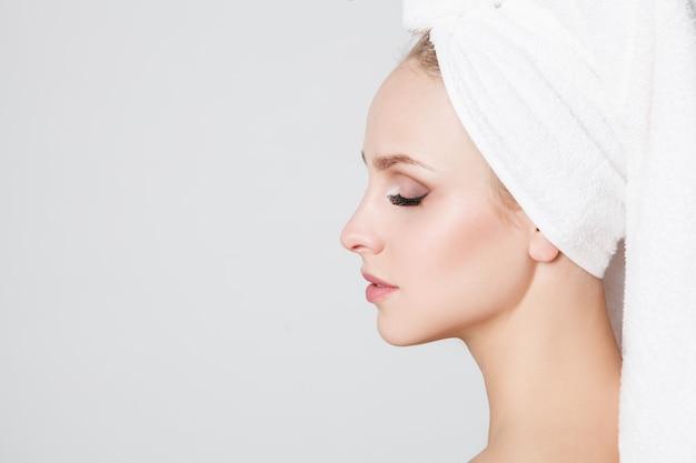 Jeugdvrouwen met handdoek op haar hoofd die camera bekijken. indoor. huidsverzorging