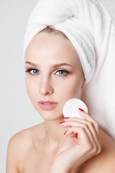 Jeugdvrouwen met handdoek op haar hoofd. make-up verwijderen met wattenschijfje