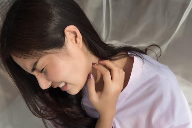 Jeukende vrouw die haar halshuid krabt
