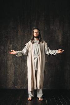 Jezus christus in wit gewaad bidden met open armen. zoon van god, christelijk geloof