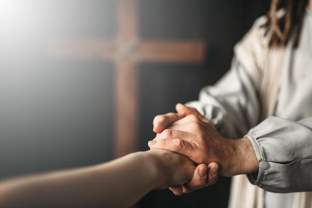 Jezus christus in wit gewaad geeft de gelovigen een helpende hand