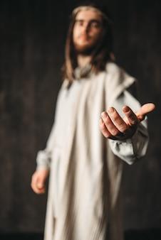 Jezus christus in wit gewaad strekt zijn hand uit,