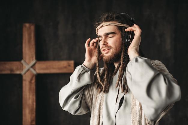 Jezus christus luisteren naar muziek met een koptelefoon, kruisiging kruis op zwart