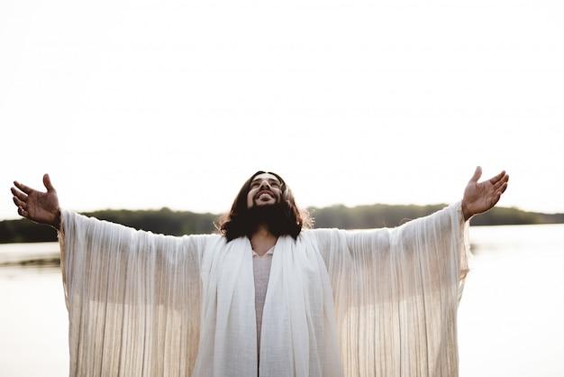 Jezus christus met zijn handen naar de hemel