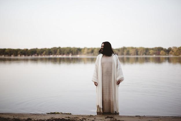 Jezus christus staat in het water in de buurt van de kust terwijl u in de verte kijkt