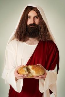 Jezus deelt het brood in stukjes
