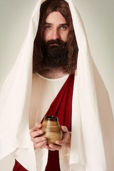 Jezus draagt een mantel met wijwater op de kruik