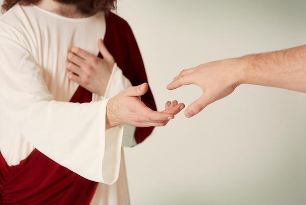Jezus reddende hand die reikt naar de gelovigen