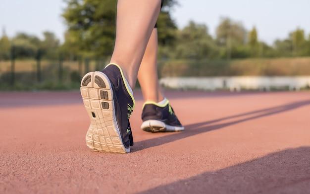 Jigger-vrouw die sneakers draagt en op de grond jogt