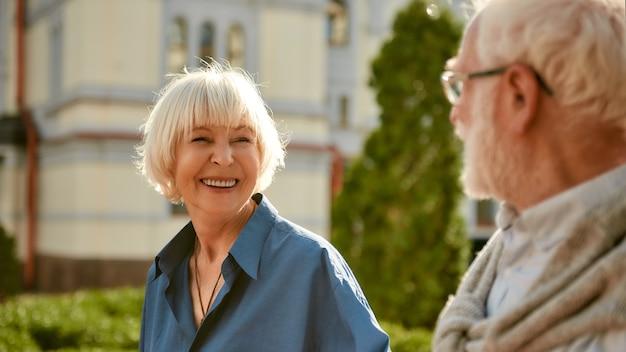 Jij bent mijn leven gelukkig en mooi bejaarde echtpaar dat naar elkaar kijkt en glimlacht tijdens het lopen