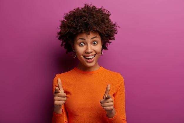 Jij bent wat ik nodig heb. positieve gekrulde vrouw wijst naar je, staart met plezier, wil dat je je bij haar team voegt, lacht vriendelijk, draagt oranje poloneck, poseert over paarse muur, wijst naar voren