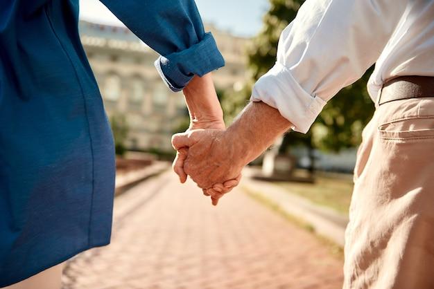 Jij en ik voor altijd close-up van bejaarde echtpaar hand in hand terwijl ze samen buiten wandelen
