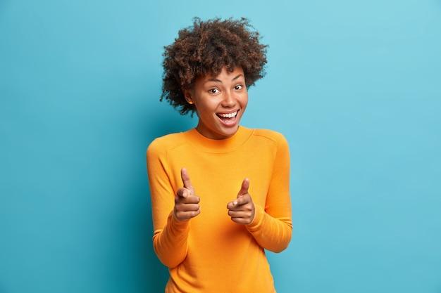 Jij hebt het. gelukkige jonge krullende vrouw met krullend haar wijst naar camera met wijsvingers pakt iemand glimlacht in grote lijnen geïsoleerd over blauwe studiomuur