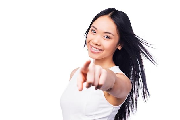 Jij kiest! mooie jonge aziatische vrouw in mooie jurk die naar de camera wijst en glimlacht terwijl ze tegen een witte achtergrond staat