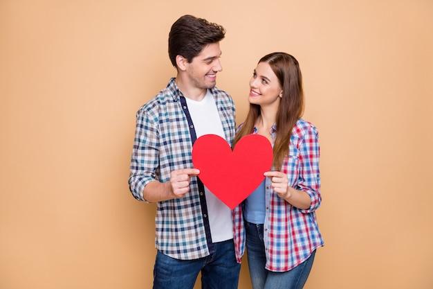 Jij mijn wereld! portret van romantische getrouwde echtgenoten houden rode grote papercard hart blik geniet 14 februari droom datum slijtage geruit hemd geïsoleerd op beige kleur achtergrond