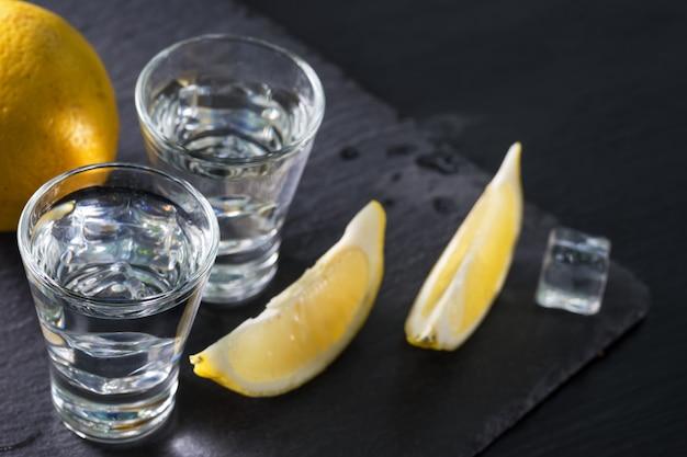 Jin of wodka in glazen met partjes citroen en ijs