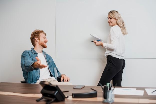 Jobcollega's praten en schrijven op een whiteboard