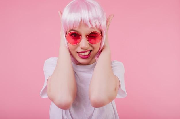 Jocund aantrekkelijk vrouwelijk model in zonnebril die haar oren behandelt. schattig meisje met roze haar geïsoleerd op pastel muur