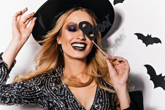 Jocund blond meisje dat van halloween-feest geniet. blithesome vrouwelijk model in hoed poseren met vleermuizen op muur.