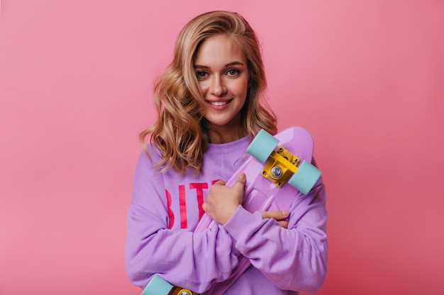 Jocund lachende vrouw met paars skateboard. stijlvol fascinerend meisje met blond haar lachend op pastel.