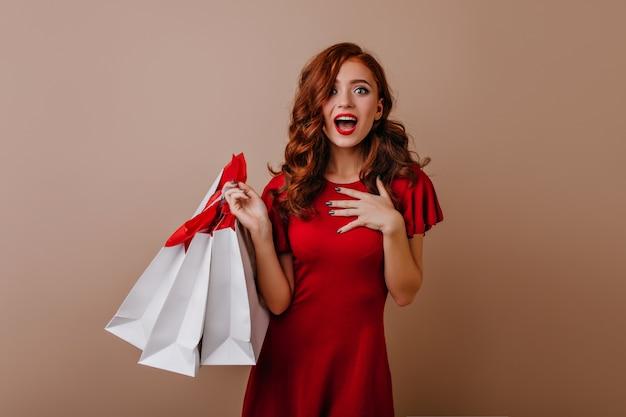 Jocund langharige jonge vrouw poseren na het winkelen. zorgeloze gember dame met winkelzakken.