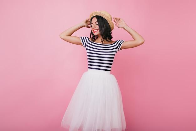 Jocund latijns-vrouw met zwart haar poseren met gesloten ogen. indoor portret van vrij gelooid meisje genieten van fotoshoot.