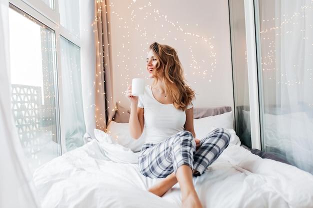 Jocund meisje in nachtkleding venster kijken. prachtig vrouwelijk model in pyjama's vroeg in de ochtend genieten van koffie.