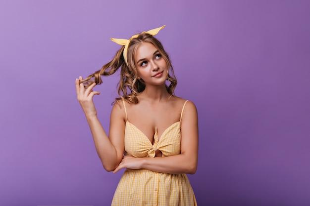 Jocund peinzend meisje speelt met haar golvende blonde haar. sensuele gelooide vrouw in gele jurk staande op paars.