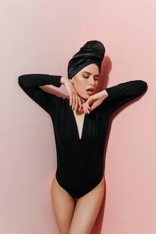 Jocund vrouwelijk model poseren in zwarte tulband en romper