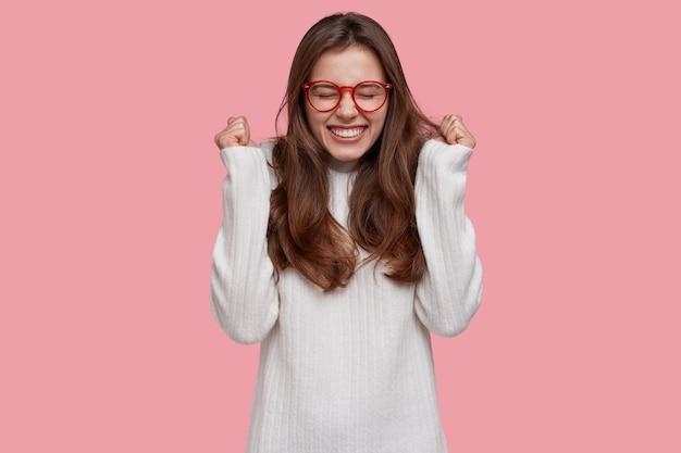Joful triomfantelijke jonge vrouw balde vuisten in overwinningsgebaar, glimlacht broady van tevredenheid, verheugt zich over de overwinning, heeft lang donker haar
