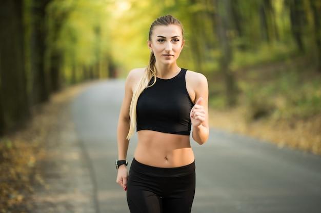 Joggende vrouw loopt in het park in de zon op een mooie zomerdag. sport fitness model kaukasische etniciteit training buiten voor marathon.