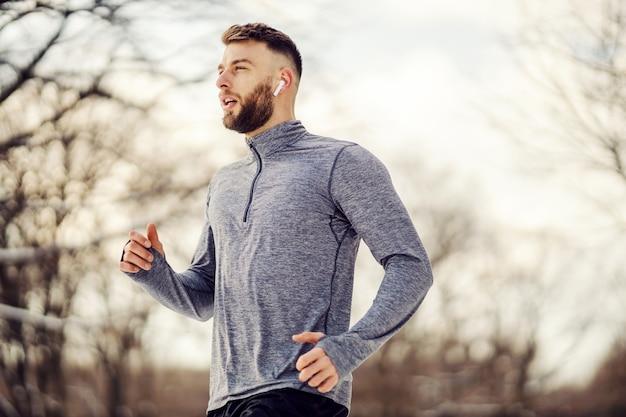 Jogger joggen in de natuur op besneeuwde winterdag. wintersport, koud weer, gezonde gewoontes