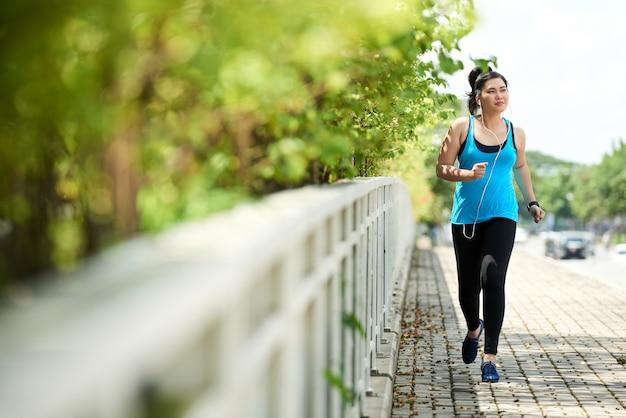 Joggingsmeisje dat in openlucht met oortelefoons loopt die aan muziek luisteren