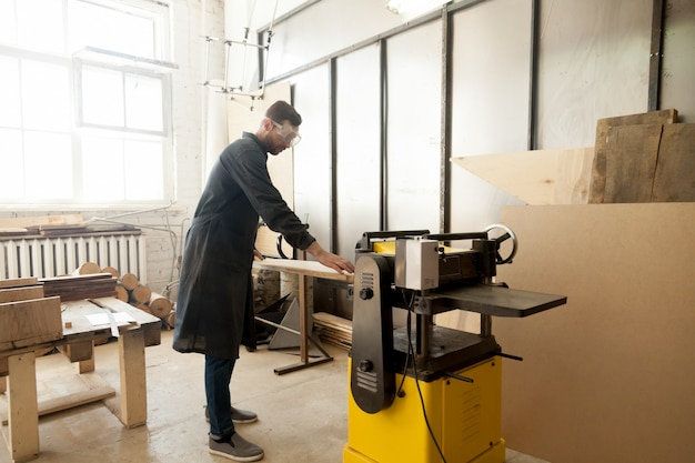 Jointer in beschermende werkkleding verwerken hout op stationair gereedschap