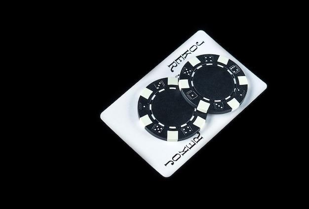Jokerkaart en fiches in de winnende combinatie op de zwarte achtergrond bij een pokerclub of casino