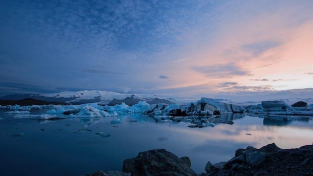 Jokulsarlon, gletsjerlagune in ijsland bij nacht met ijs dat in water drijft.