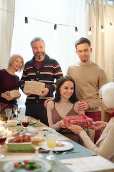 Jong aanhankelijk paar kerstcadeau in geschenkdoos geven oma vergadering door feestelijke tafel geserveerd na het diner