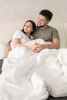 Jong aanhankelijk rustgevend stel dat 's ochtends op een comfortabel bed ontspant en opzij kijkt terwijl ze iets aangenaams bespreken