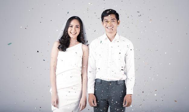 Jong aantrekkelijk aziatisch stel, man met wit overhemd, vrouw met witte jurk met bruidssluier die samen staat. concept voor pre-huwelijksfotografie.