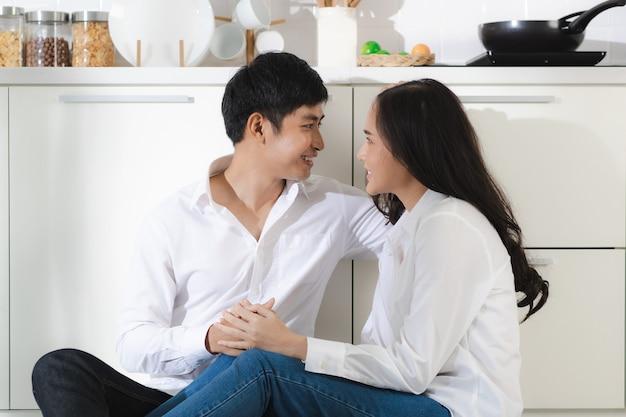 Jong aantrekkelijk aziatisch stel met een wit overhemd en een spijkerbroek die samen in de witte keuken zitten