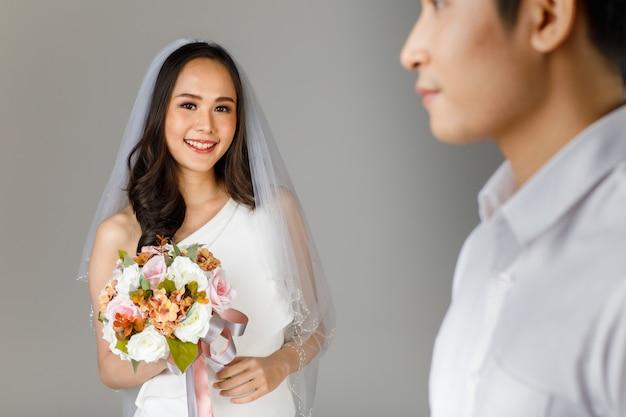 Jong aantrekkelijk aziatisch stel, selectieve focus op bruid die een bruidsjurk draagt met een sluier die een bloemboeket vasthoudt. wazige man met wit overhemd op de voorgrond. concept voor pre-huwelijksfotografie.