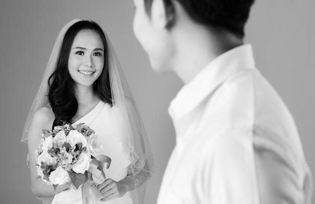 Jong aantrekkelijk aziatisch stel, selectieve focus op bruid die een bruidsjurk draagt met een sluier die een bloemboeket vasthoudt. wazige man met wit overhemd op de voorgrond. zwart en wit.