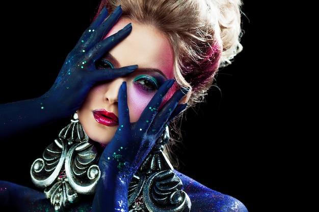 Jong aantrekkelijk blondemeisje in heldere kunst-make-up, hoog haar, lichaam het schilderen. steentjes en glitter