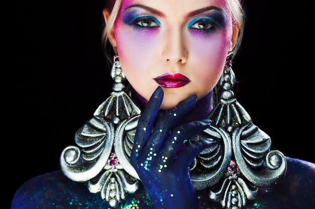 Jong aantrekkelijk blondemeisje in heldere kunst-make-up, wat betreft lippen